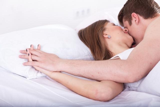 ベッドで手を重ねるカップル